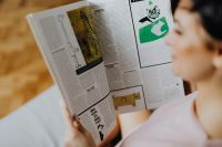 Kaboompics - A woman with short dark hair reads a newspaper