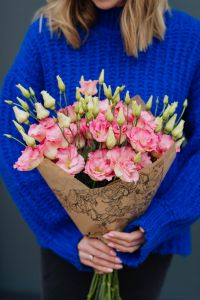 Kaboompics - Close up of woman holding bouquet of pink lisianthus flowers wrapped in brown paper