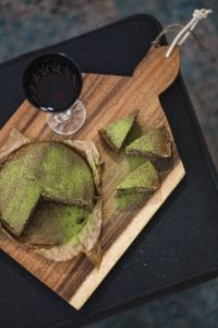 Kaboompics - Delicious homemade matcha cake on a wooden board with wine
