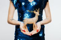 Kaboompics - Woman in Blue Dress Holds Gold Reindeer
