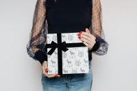 Kaboompics - Woman in Black Blouse Holds a Christmas Gift