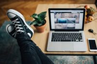 Kaboompics - Woman in ripped jeans and black sneakers with a silver laptop on a wooden table