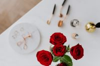 Red roses, gold rings, perfume brushes and make-up accessories on white marble