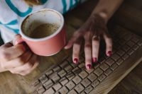 Kaboompics - Woman with wireless wooden keyboard and cup of coffee