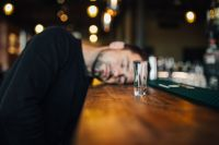 Kaboompics - Drunk and unconscious man lying on a counter in a classy bar