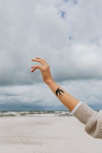 Kaboompics - A woman's hands with a swallow tattoo raised to the sky