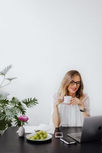 A businesswoman drinks coffee in the office at her desk