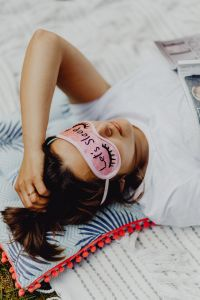 Kaboompics - Joyful girl relaxing in bedroom - top view of brunette women in pink sleeping mask