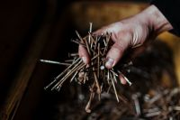 Kaboompics - Man grabbing a heap of rusty nails