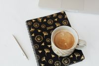 Organizer & cup of coffee on marble table