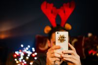 Kaboompics - A handsome man with Christmas presents takes pictures with his phone