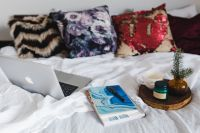Bed full of pillows and notebooks with Apple gadgets