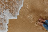 Closeup of sand, feet and small wave