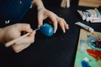 Kaboompics - Woman Painting Blue Easter Eggs
