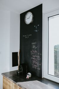 Kaboompics - Kitchen clock with a daily schedule on a blackboard