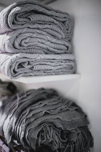 Kaboompics - Grey woolen fabric stacked on shelves