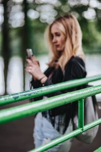 Kaboompics - Blonde woman in a black jacket and ripped jeans by a green handrail