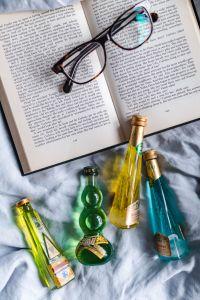 Kaboompics - Group of colorful little bottles with liqueurs & book with glasses