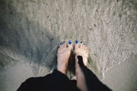 CLOSEUP OF GIRL'S LEGS AT SEASIDE
