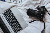 Kaboompics - Silver laptop and black camera on white bed sheets