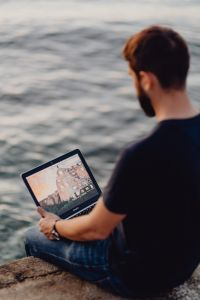 Kaboompics - A man using a Macbook laptop at the seaside