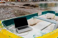 Kaboompics - Macbook laptop on a small yellow boat on the beach