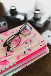 Kaboompics - Corrective glasses on a stack of notebooks