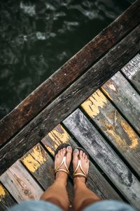 Kaboompics - Detail of the legs of a woman standing at the edge of the pier