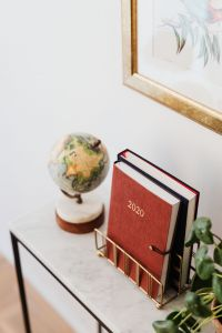 Kaboompics - Planner on The White Marble Table, White Background, Pilea, Globe, Painting on the Wall
