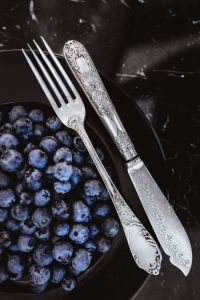 Kaboompics - Fresh blueberries on a black plate with vintage cutlery