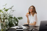 A businesswoman eats a hamburger at work