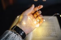 Female hand, fairy lights, book