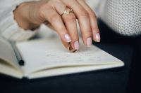 Kaboompics - Woman holding a ring over a notebook