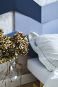 Kaboompics - An ornamental golden plant in a jar by the bed with white sheets