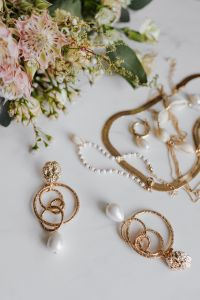 Kaboompics - Gold jewellery on white marble - necklace, bracelets, earrings, flowers