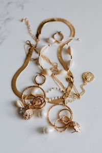 Kaboompics - Gold jewellery on white marble - necklace, bracelets, earrings