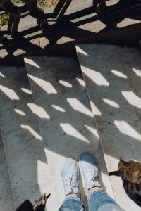 Kaboompics - A woman dressed in blue jeans and sneakers is standing on a white marble staircase