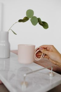Kaboompics - A woman's hand holds a pink mug or cup over a marble tray