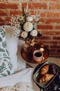 Kaboompics - Croissants and figs on a green plate, a cup of coffee and a candle