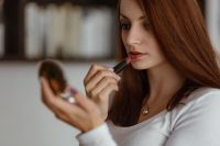 Kaboompics - Young beautiful woman doing her make up with lipstick