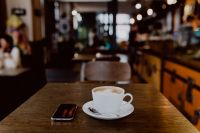 Kaboompics - Cup of coffee on table in cafe, iPhone mobile phone