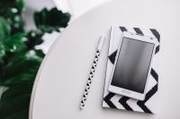 Kaboompics - Black-and-white notebook and a white smarphone with various items