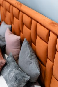 Kaboompics - Upholstered orange bed - pillows