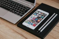 Kaboompics - Silver Acer laptop, a white Apple iPhone and a black notebook on a wooden desk