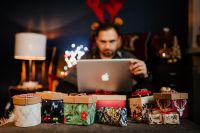 Kaboompics - A handsome man with Christmas presents - using MacBook laptop