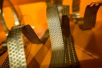 Kaboompics - Bended golden metal on an orange background