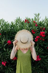 Kaboompics - A smiling woman in a summer hat with pink flowers