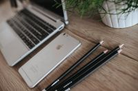 Kaboompics - Silver Acer laptop on a wooden desk with a green plant, pencils and an Apple iPhone