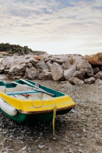 Kaboompics - Little yellow green boat on the beach
