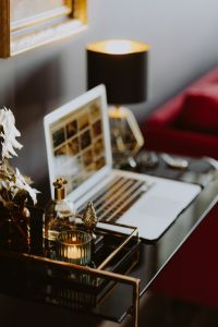 Kaboompics - Elegant home office with golden accessories. MacBook, candle, fragrances